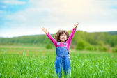 Happy little girl with her hands up on the green wheat field — Stock Photo