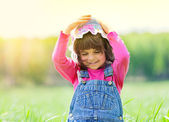 Happy little girl on the meadow in sunny day — Stock Photo