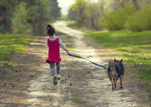 Little girl with dog running on the road — Stockfoto