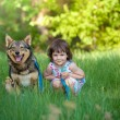 Happy little girl with dog sitting on the grass — Stock Photo