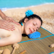 Pretty young woman relaxing on the beach during massage — Stock Photo