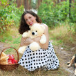 Stock Photo: Pretty girl with dog and toy bears siting in the wood