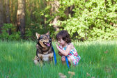 Happy little girl playing with dog on the grass — Stockfoto