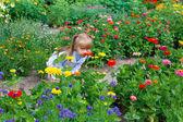 Happy little girl smelling the flower on the flower lawn — Stok fotoğraf
