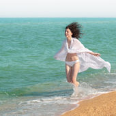 Young happy woman running on the beach — Stock Photo