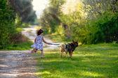 Little girl with dog running on the road to the sun — Stockfoto