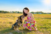 Pretty young girl and dog smiling each other — Stock Photo