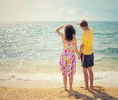海滩上的手牵着手对年轻夫妇带回相机和看海 — 图库照片