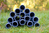 Pipes stacked on the grass — Stock Photo