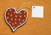 Heart shaped cookie with card on cork surface — Stock Photo