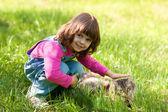 Malá dívka si hraje s kočkou na trávě — Stock fotografie