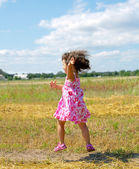 Crying little girl staying on the meadow — Stock Photo