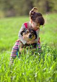 Happy little girl straddled the dog — Stockfoto
