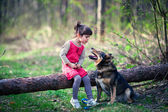 Happy little girl with big dog in the forest — Stock Photo