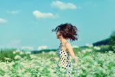 Young happy girl walking on the buckwheat field — Stock Photo