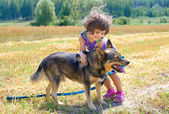 Happy little girl playing with dog — Stock Photo
