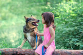 Happy little girl with dog sitting — Stockfoto