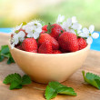 Stock Photo: Strawberries in plate on wicker tablecloth