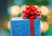 A blue gift with a red ribbon on Christmas — Stock Photo