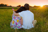 Young couple sitting back to camera on the grass and looking at sunset — Stock Photo