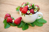Strawberries in a white cap decorated with flowers and leaves — Stock Photo
