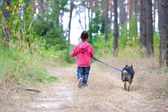 Little girl with dog running on the road in the wood — Stock Photo