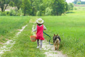 Little girl with dog running on the road to the picnic — Stock Photo
