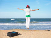 Young happy girl wearing Santa's hat jumping on the beach — Stock Photo