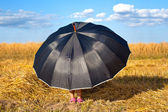 Little girl hiding under big black umbrella in fair weather — Stock Photo