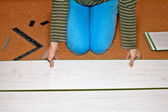 Woman laying laminate floor — Stockfoto