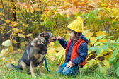 Girl playing with dog in the forest — Stock Photo