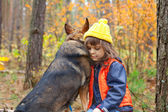 Sad  little girl with big dog in the forest — 图库照片