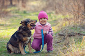 Little girl with dog in the forest — Stock Photo