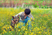 Boy with his dog on the flower meadow — Stock Photo