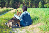 Boy sitting with his dog on the meadow — Stock Photo
