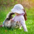 Girl playing with cat on the grass — Stock Photo