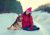 Young woman  hugging dog in snowstorm — Stock Photo