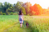 Young woman with dog walking — Stock Photo