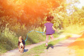 Girl with dog running in the countryside — Stock Photo