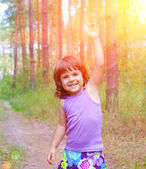 Little girl with hand up in the forest — Stock Photo