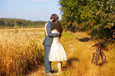Couple hugging over wheat field — Stock Photo