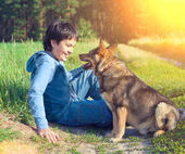 Boy  talking to dog in the meadow — Stock Photo