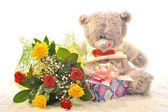 Flowers and a teddy bear — Stock Photo