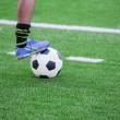 pés do jogador de futebol, pisando em uma bola de futebol — Fotografia Stock  #48657805