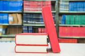 A pile of books with library on the background — Stockfoto