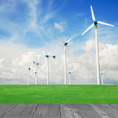 Wind mill power plant in green field and wood plant against blue — Stock Photo