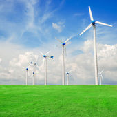 Wind mill power plant in green field  against blue sky — Stock Photo