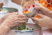 Pour water on the hands of revered elders and gives blessing in  — Stock Photo