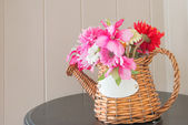 Bouquet of flowers in watering can on wooden table  — Stock Photo