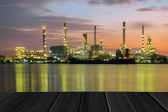 Wood planks floor with Oil refinery plant at twilight background — Stock Photo
